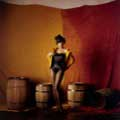 Wearing a bustier and stockings, Diahann Carroll is playful in her yellow fitted jacket and top hat with wooden barrels in the background. This 1960 image by Milton H Greene was taken during Diahann's album cover session.