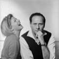 Eli Wallach has a serious look on his face as he stares directly at the camera with his left arm to his chin while his wife, Anne Jackson is seated to Eli's right and laughing. This black and white photograph was taken by Milton H Greene in his New York studio for Glamour magazine in 1964.