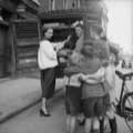 Milton Greene took this vintage Irish fashion photograph while on assignment for Life Magazine in 1953. Model Lisa Fonssagrives stands at a bread cart wearing a bandanna and a cute white jacket while holding bread and looking playfully at a group of children gathered to the right. Milton was in Ireland photographing rising designer Sybil Connelly.