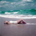 This classic fashion photograph was taken in 1954 by Milton H. Greene while on assignment for look Magazine. Wearing vintage white one-piece bathing suit, model Carmen is laying on the Manalapan Beach, Florida sand getting some sun while the ocean waves crash just behind her.