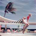 Models Carmen and Dorothy Tristan are having fun on a diving board in the classic vintage fashion color image by Milton H. Green. On assignment for Look Magazine in 1954, one model is laying on the diving board wearing a black and white striped 1950s era bathing suit and leaning on a blonde model who is laughing and looking at the camera wearing a red and white outfit.