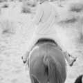 Candid black and white photograph of Marilyn Monroe wearing white courdoroy suite and black head band looking back on horse back in California by Milton H. Greene in 1954.
