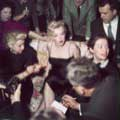 Milton H Green took this classic photo of a stunning Marilyn Monroe wearing a black spaghetti dress while speaking to reporters during a cocktail party in 1956. The reporters have surrounded Marilyn as she calmly answers a question while sitting on a couch in Greene's home.