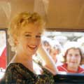 This shot of Marilyn Monroe was taken by Milton H Greene on the set of Bus Stop in 1957. Photographed from inside of a car, Marilyn is smiling at the camera as she is chauffeured through a crowd of people.