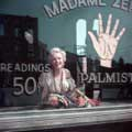 In an image from the popular The Gypsy Sitting, Marilyn Monroe is smiling widely behind the window of a gypsy palm reader shop on the 20th Century Fox back lot. Milton H Greene took this photo in 1956.