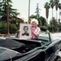 Wearing a red checkered shirt, Marilyn Monroe is smiling while holding a framed photo of her idol, Abraham Lincoln. Taken by Milton H Greene in Los Angeles 1954, Marilyn is standing in her brand new black Cadillac given to her by Jack Benny. Palm trees can be seen in the background.