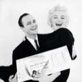 Marilyn Monroe and Marlon Brando are smiling wide as Marlon holds Marilyn with an oversized ticket to the play The Rose Tattoo, a benefit for the Actors Studio. Black and White photo by Milton H Greene in November 1955.