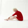Wearing nothing but a red sweater, Marilyn Monroe is seated with her legs out in front of her with her hand touching her ankles. Looking directly at the camera she is smiling against a white background. Milton H Greene took this photo in 1955.
