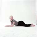Laying on the ground wearing black pants and a gray and black striped top, Marilyn Monroe is seductively looking at the camera against a white backdrop. Taken by Milton H Greene in his New York Studio in 1956.
