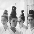 Legendary Fashion photographer Milton H. Greene snapped this classic black and white vintage fashion image in Paris 1962. Four models have their hair up in unique, tall buns and are wearing white collared shirts. Two of the models are smiling and looking at the camera.