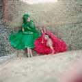 Leaning against a wall of hay, models Fiona Von Tyson and Nelly are wearing a green and red dress each with veils. This classic vintage fashion image was taken by Milton H. Greene in Spain for Life Magazine.
