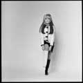 Iconic 1966 black and white photo of Nancy Sinatra standing and pulling up one boot while wearing a black and a white boot. Taken by Milton H Greene during the height of Nancy's hot song