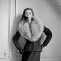 Black and white retro fashion photograph of Sophie Litvak is taken in 1952 by Milton H. Greene for Life Magazine in Paris. Sophie Litvak is wearing an all black assemble with a large fur coat looking downwards and her arms bent with her hands on her sides.